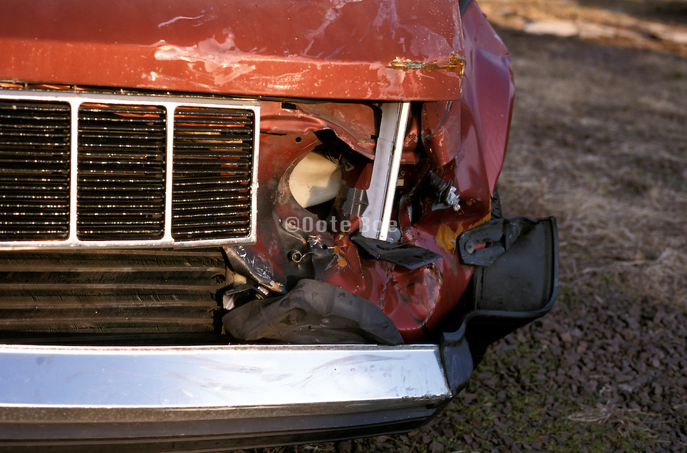 Close up of a broken headlight on a red truck