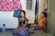 30 APRIL 2013 - MAHACHAI, SAMUT SAKHON, THAILAND:   Burmese women watch television in their apartment in the Thai fishing port of Mahachai. The Thai fishing industry is heavily reliant on Burmese and Cambodian migrants. Burmese migrants crew many of the fishing boats that sail out of Samut Sakhon and staff many of the fish processing plants in Samut Sakhon, about 45 miles south of Bangkok. Migrants pay as much $700 (US) each to be smuggled from the Burmese border to Samut Sakhon for jobs that pay less than $5.00 (US) per day. There have also been reports that some Burmese workers are abused and held in slavery like conditions in the Thai fishing industry.         PHOTO BY JACK KURTZ