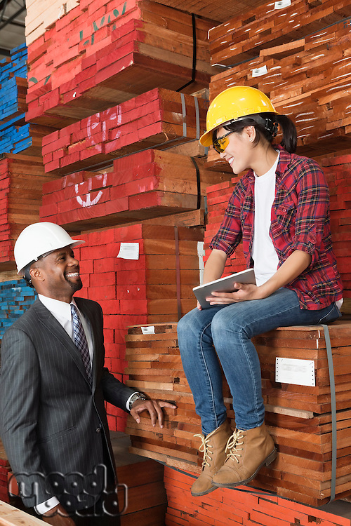 Female industrial worker and male engineer smiling while looking at each other at timber yard