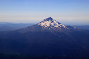 "This aerial view of Oregon's Mount Hood illustrates how rapidly it rises from sea level to 11,249 feet (3,429 m). Hood is Oregon's tallest mountain. The USGS considers it a ""potentially active"" volcano, with as much as 7 percent chance it will erupt within the next 30 years."