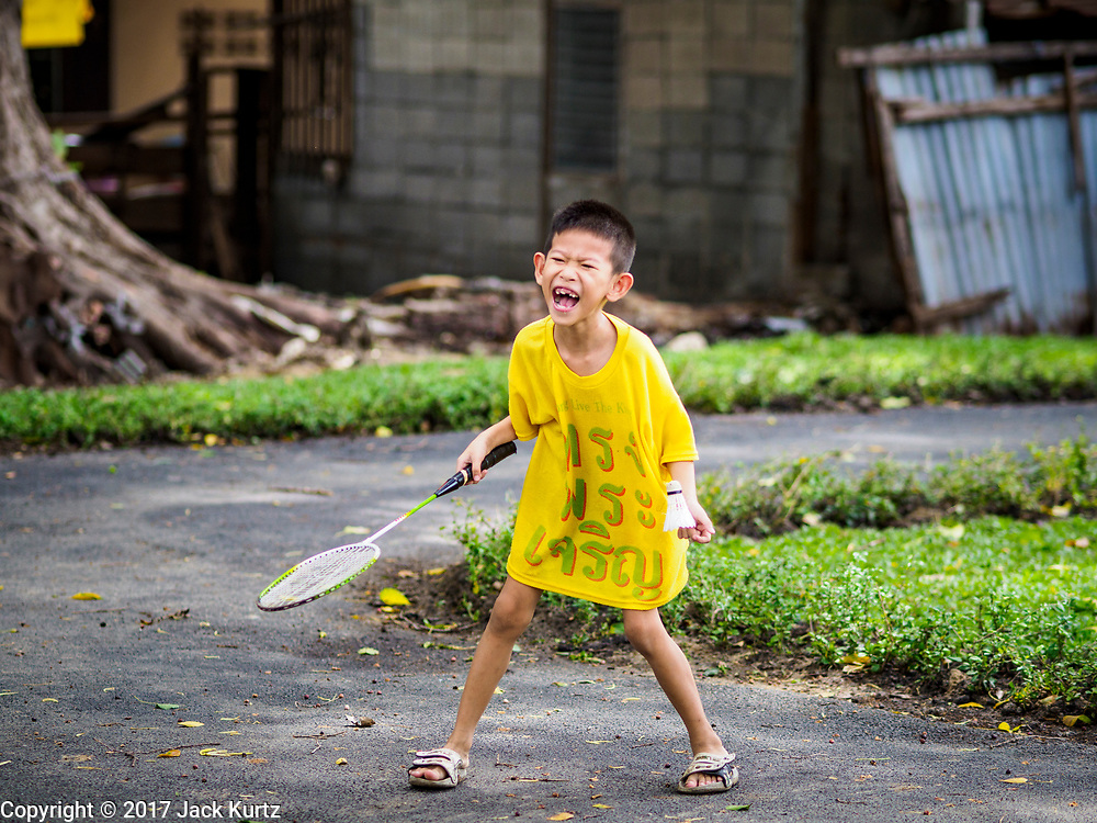 20 MAY 2017 - BANGKOK, THAILAND:  A boy who lives in Pom Mahakan gets ready to serve the badminton shuttlecock during a game in the new park in Pom Mahakan.  The park was built after the families living on the site were evicted and their homes razed. The final evictions of the remaining families in Pom Mahakan, a slum community in a 19th century fort in Bangkok, have started. City officials are moving the residents out of the fort. NGOs and historic preservation organizations protested the city's action but city officials did not relent and started evicting the remaining families in early March.       PHOTO BY JACK KURTZ