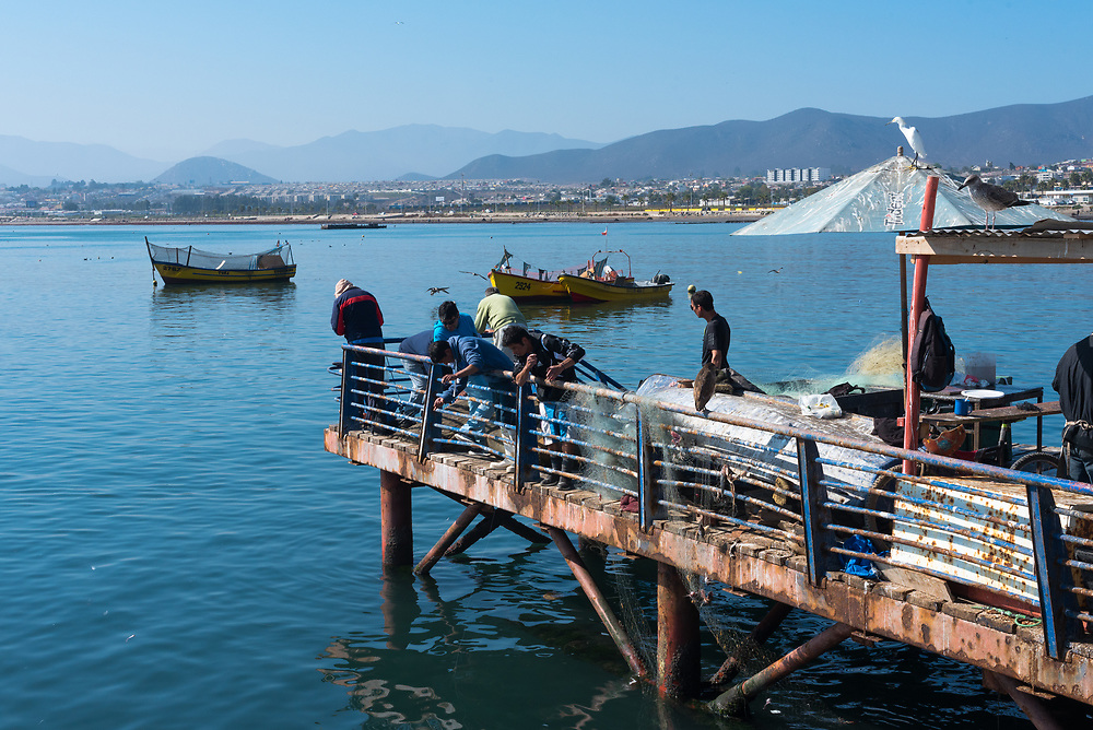 Coquimbo, Chile--April 7, 2018. Fishermen cast their lines from a pier in the port city of Coquimbo, Chile. Editorial Use Only.