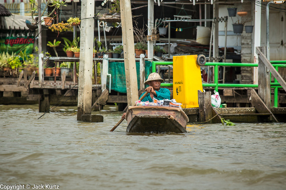"17 NOVEMBER 2012 - BANGKOK, THAILAND:  A man paddles his canoe on a khlong, or canal, in the Thonburi section of Bangkok. Bangkok used to be known as the ""Venice of the East"" because of the number of waterways the criss crossed the city. Now most of the waterways have been filled in but boats and ships still play an important role in daily life in Bangkok. Thousands of people commute to work daily on the Chao Phraya Express Boats and fast boats that ply Khlong Saen Saeb or use boats to get around on the canals on the Thonburi side of the river. Boats are used to haul commodities through the city to deep water ports for export.    PHOTO BY JACK KURTZ"