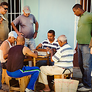 Cuban men playing a game of Dominos on the street in the historic town of Trinidad, Cuba.