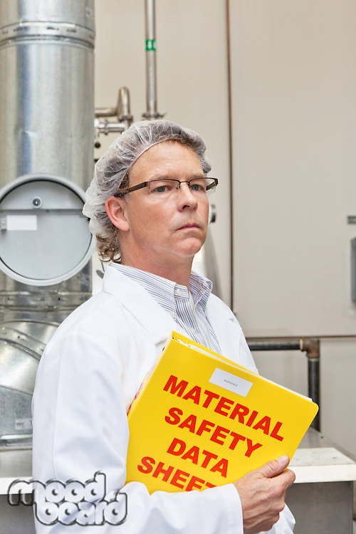 Middle-aged man holding data sheets of factory