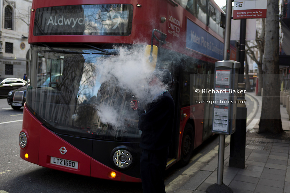 Exhaling vape smoke clouds around his head, a bus driver vapes during his break, in front of his Routemaster bus parked at Aldwych in central London, on 6th March 2020, in London, England.