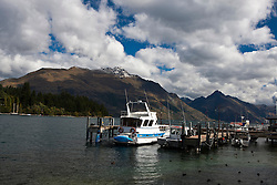 A boat is docked along the shores of Lake Wakatipu, Queenstown, Otago District, South Island, New Zealand