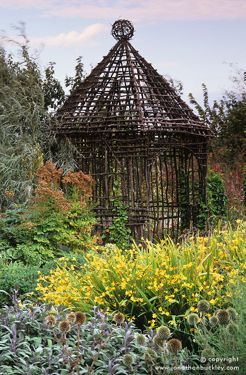 A rustic, woven twig summer house in early autumn