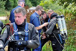 © licensed to London News Pictures. RICHMOND, UK.  01/08/11. Police divers check their equipment. The Metropolitan police search the River Thames near Richmond, London, today (1 Aug 2011) after a 17 year boy went missing after taking part in a kayak competition.  Mandatory Credit Stephen Simpson/LNP