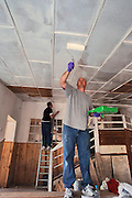 Master Sgt. Brad Bush, appears to be a giant while standing on scaffolding boards, as he applies the first coat of white paint on the slanted ceiling of what will be a reception room. The Devine, Tex. native is deployed to the 276th Expeditionary Logistics Readiness Squadron from the 509th Bomb Wing. The Bishkek International Womens Club describes the home as being at the foot of the snow-decked mountains of the Tien-Shan range in the little village Kok Jar [.. over the o] (Schar) just outside Bishkek, Kyrgyz Republic, there used to be a small center where groups of handicapped children could receive therapeutic treatment over a periods of three weeks and where 8-10 homeless disabled children used to live. This center was part of the Hadjeshda Children?s Center, today housing more than 60 children and teenagers. However, in April 2004 the roof burned down and the other parts of the house were badly damaged.  Today more than 120 children are still waiting for the center to re-open. (U.S. Air Force photo by Master Sgt. Lance Cheung)<br />