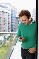 Man text messaging on balcony