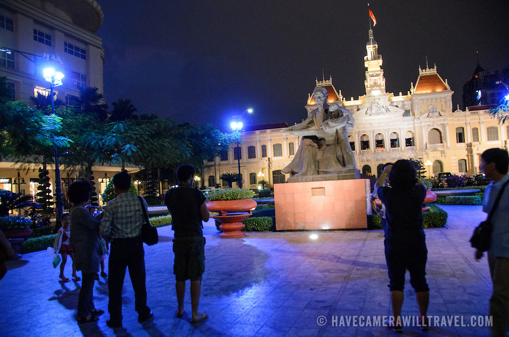 Tourists take photos of the statue of Uncle Ho (Ho Chi Minh) in front of city hall in central Saigon. Ho Chi Minh City Hall was built in the early 20th Century by the French colonial government as Saigon's city hall. It's also known as Ho Chi Minh City People's Committee Head office, in French as Hôtel de Ville de Saigon, and in Vietnamese as Tr? s? ?y ban Nhân dân Thành ph? H? Chí Minh.