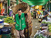 "21 DECEMBER 2015 - BANGKOK, THAILAND:  Porters in Pak Khlong Talat, also called the Flower Market. The market has been a Bangkok landmark for more than 50 years and is the largest wholesale flower market in Bangkok. A recent renovation resulted in many stalls being closed to make room for chain restaurants to attract tourists. Now Bangkok city officials are threatening to evict sidewalk vendors who line the outside of the market. Evicting the sidewalk vendors is a part of a citywide effort to ""clean up"" Bangkok.      PHOTO BY JACK KURTZ"