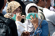 Padang, Western Sumatra, Indonesia, 7th October 2009:?Two women cover their faces to protect against the dust, smell and disease near the Ambacang Hotel in Padang following a devastating earthquake in Western Sumatra that claimed the lives of an estimated 2000 people.?Photo: Joseph Feil