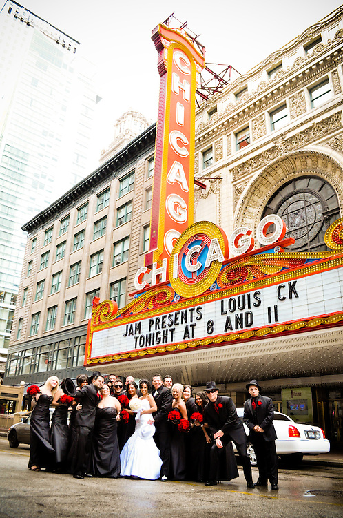 Tara & Randy's bridal party stops traffic for a portrait in front of the Chicago Theatre