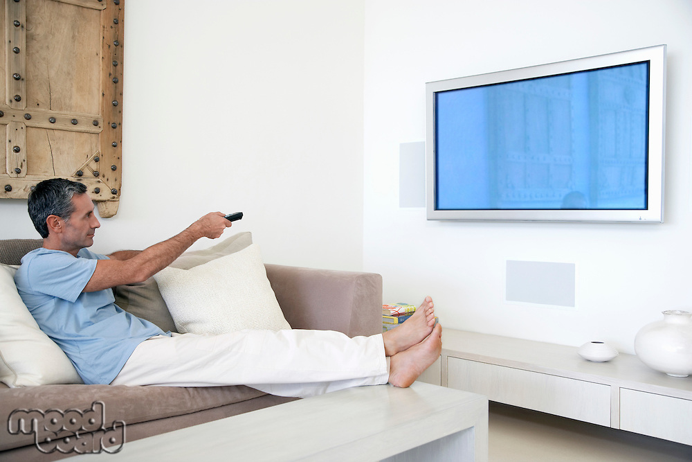Man using remote control reclining on couch in living room side view