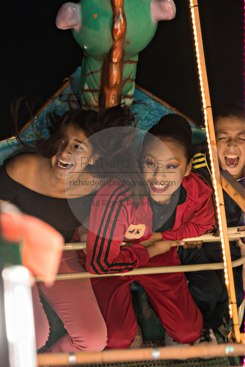 Young Mexican girls react to an amusement ride at a traveling carnival during celebrations marking the Day of the Dead festival n the tiny Purepecha town of Ihuatzio, Michoacan, Mexico.