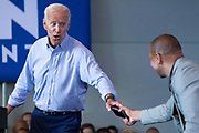Former Vice President Joe Biden hands State Senator Marlon Kimpson, right, his mobile phone after it rang during a town hall meeting at the International Longshoreman's Association Hall July 7, 2019 in Charleston, South Carolina.