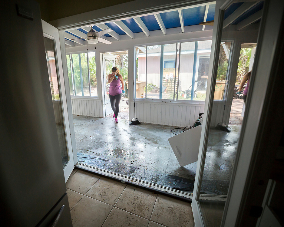Cheryl M. Smith makes multiple trips to the trash to throw out food ruined by flood water, Tuesday, Sept., 12, 2017, on Tybee Island, Ga., after Tropical Storm Irma flooded her house with three feet of water. (AP Photo/Stephen B. Morton)