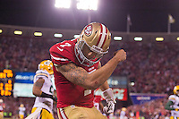 12 January 2013: Quarterback (7) Colin Kaepernick of the San Francisco 49ers runs the ball for a touchdown and celebrates by kissing his biceps and tattoos against the Green Bay Packers during the second half of the 49ers 45-31 victory over the Packers in an NFL Divisional Playoff Game at Candlestick Park in San Francisco, CA.