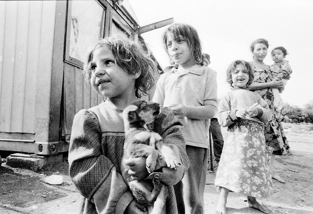 Roma children in a makeshift camp in Kraljevo. ..Romas children do not receive the same attention as the other IDPs children: they do not go to school and they do not receive any assistance as far as health is concerned. Because the families did not have documents, they could not be registered officially as IDPs...During the summer1999, over 245,000 Serbs and Roms fled to Serbia and Montenegro from or within Kosovo in fear of reprisals from the majority Albanian population, after NATO air strikes had forced the withdrawal of Yugoslav. In 2003, less than 2% of them had returned and a large number of these internally displaced persons (IDPs) were still living in camps in very difficult conditions..In addition, around 5,000 IDPs, mainly of Roma ethnicity, are living in unrecognized collective centres, makeshift huts, corrugated metal containers and other substandard shelters. .This work was meant to look at how the life of children and young adults is affected by the fact that they are IDPs. I asked myself more specifically what would be different for these children/young adults from the 'normal' people of their age as far as education, health, social life, family, 'love' life and leisure are concerned. ..Enfants roms dans un camp improvisé de Kraljevo. Les enfants roms ne vont pas à l'école et ne reçoivent aucune assistance médicale. Faute de papiers d'identité, ils n'ont pu être officiellement enregistrés en tant qu'IDP...Pendant l'été 1999, plus de 245 000 serbes et roms ont fuit le Kosovo pour chercher refuge en Serbie ou au Montenegro, par peur de représailles de la part de la majorité de la population albanaise après que les forces de l'OTAN aient forcé l'armée yougoslave à se retirer. En 2003, moins de 2% d'entre eux étaient rentrés chez eux et le plus grand nombre de ces 'déplacés' (IDPs) vivaient encore dans des centres d'accueil dans des conditions très difficiles..Environ 5 000 IDPs, la plupart romas, vivent dans des centres non reconnus faits de containers