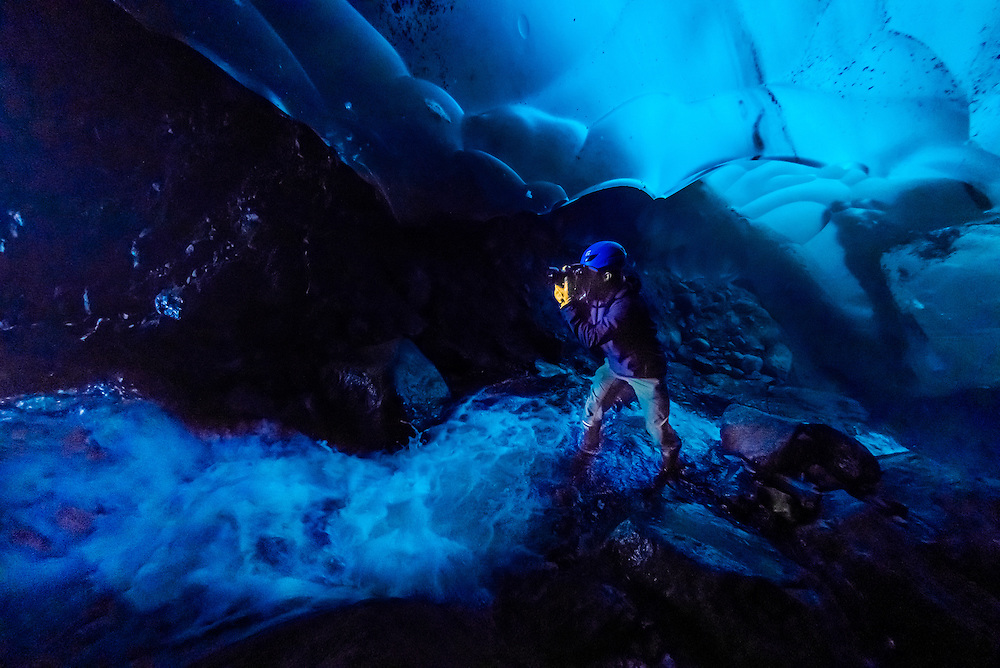 Photographing inside an ice cave under the Mendenhall Glacier, Juneau, Alaska USA.