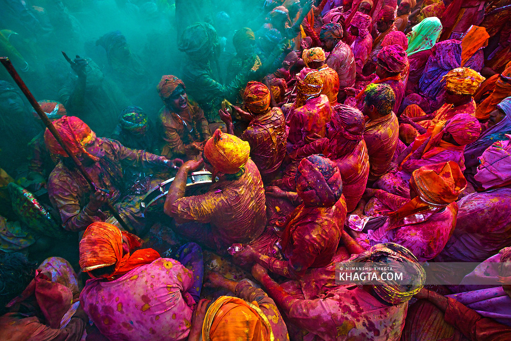 People of Braj Region of Mathura, celebrating, Holi, 'the festival of colors' in Nand Gaon Village of India.<br /> <br /> People sit together and sing and abuse each other in braj language while others throw colored powder and water on them.