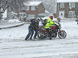 © Licensed to London News Pictures. 27/02/2018. Medway, UK. Two men attempt to push a motorbike up a hill in Medway, Kent South East England. Amber weather warnings are in place for large parts of the east of the UK as a severe cold front heads in from Russia. Photo credit: Graham Long/LNP