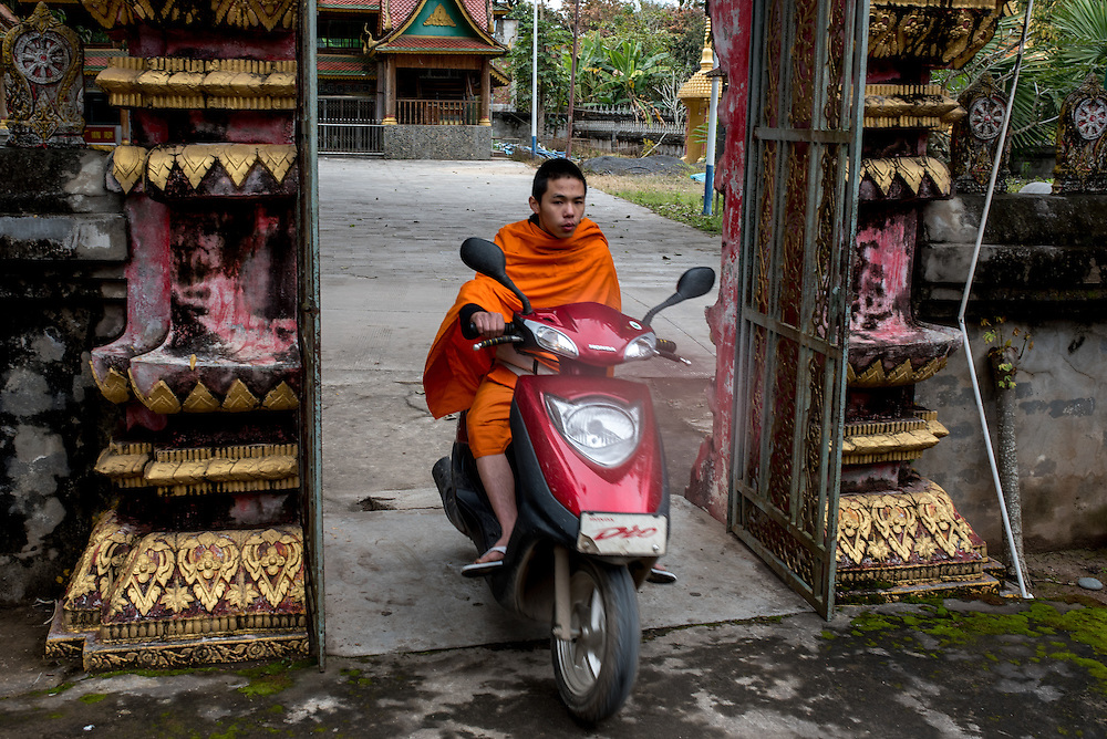 A monk drives a moto scooter in  the Olive Dam Dai cultural village in Xishuangbanna, China. The Dai are an ethnic minority living in western China as well as northern Laos, Thailand, and Vietnam. Buddhist monks are normally forbidden from operating motorized transport.