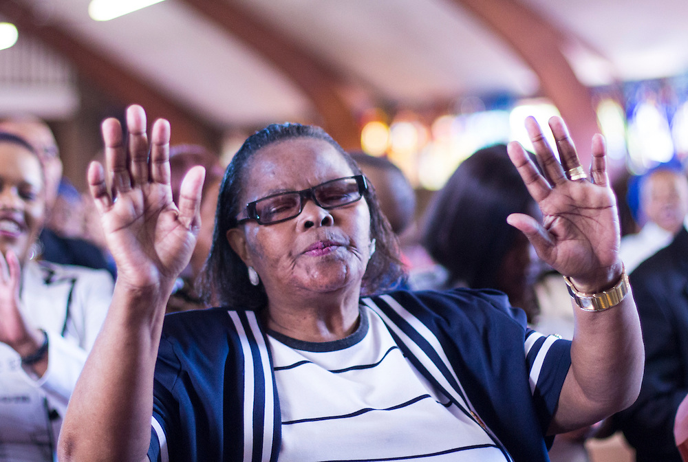A parishioner of Regina Mundi's church in Soweto raises her hands to the sky while singing during a service for former late President Nelson Mandela, on Sunday Dec.8 2013.