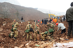 Rescuers work at the mud-inundated debris after a landslide hit Gaopo Village in Zhenxiong County, southwest China's Yunnan Province, Jan. 11, 2013. Twenty-six have been confirmed dead after the landslide hit the mountainous region on Friday morning. About 40 are believed to have been buried in the landslide, according to an initial investigation. Rescuers continue their efforts to search for the missing people, January 11, 2013. Photo by Imago / i-Images...UK ONLY