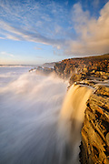 A seasonal waterfall pours into the Pacific ocean as massive winter swell pounds the Northern California Coast at Salt Point State Park.