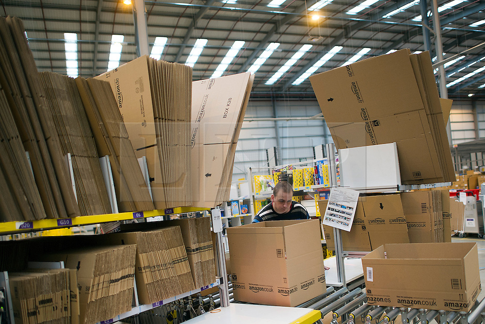© London News Pictures. 28/11/2013. Peterborough, UK. Boxes being made. Staff at the Amazon Peterborough fulfilment centre process orders as they prepare for 'Cyber Monday', busiest online shopping day of the year. On Cyber Monday 2012, Amazon.co.uk saw more than 3.5 million items ordered on the site, at a rate of around 41 items per second. Over 15000 extra staff are drafted in to Amazon nation wide over the festive period to cope with the extra demand with over 1000 extra staff being deployed at the Peterborough site. Photo credit: Ben Cawthra