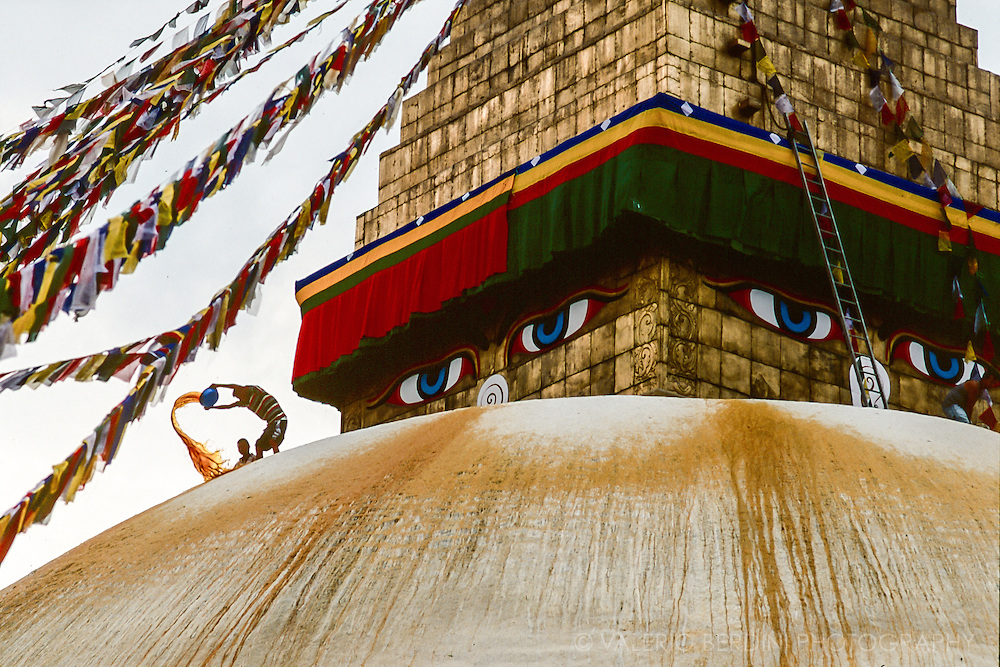 A man throws a bucket of yellow paint over the white Boudhanath stupa to depicts golden arches.