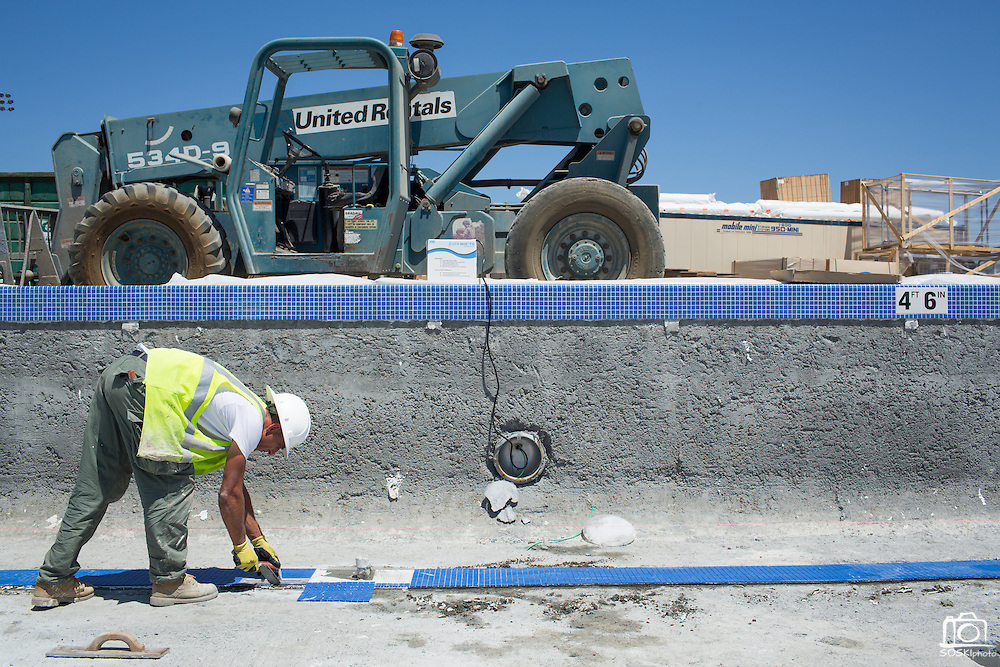 Enes Vukovic of Bosnia brushes lays lane marker tiles in the warming pool at Milpitas High School in Milpitas, California, on July 18, 2014. (Stan Olszewski/SOSKIphoto)