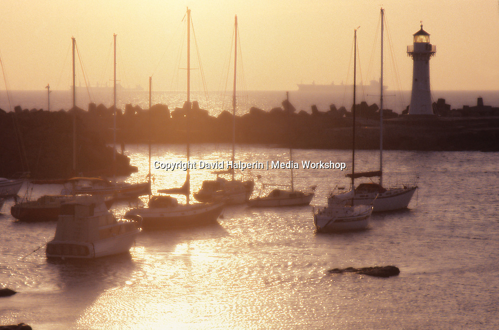 Sunrise over Pacific with harbor, lighthouse, boats, freighters