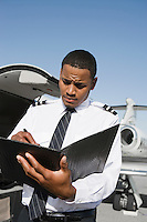 Airline pilot standing and making notes in front of airplane.