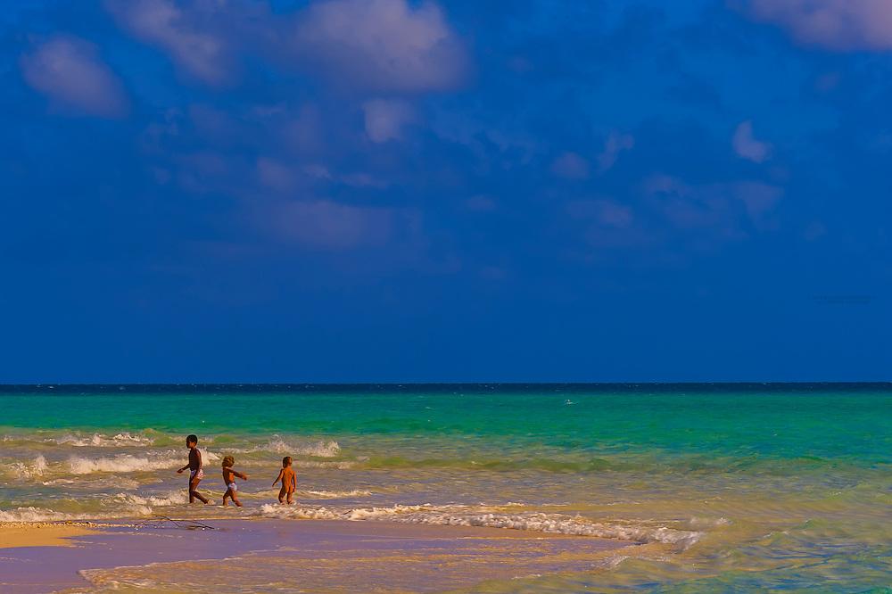 Kanak (Melanesian) boys, playing on the beach at Mouli, Island of Ouvea, Loyalty Islands, New Caledonia