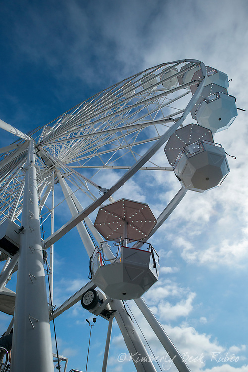 Ferris wheel photographed from below against a blue sky with soft clouds.