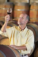Man wine-tasting aside wine casks