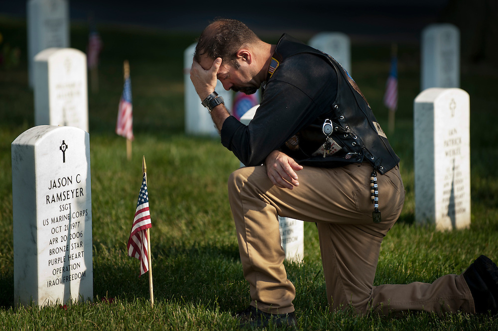 A man prays over a grave in Section 60 at Arlington National Cemetery on Memorial Day 2011.