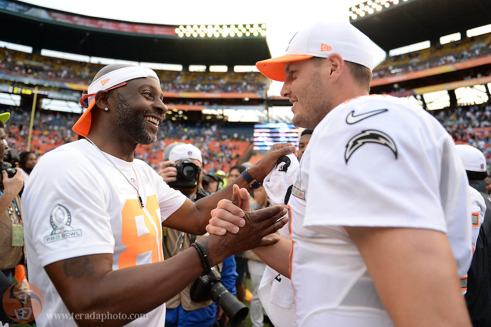 January 26, 2014; Honolulu, HI, USA; Team Rice alumni captain Jerry Rice (left) celebrates with quarterback Philip Rivers of the San Diego Chargers (17, right) after the 2014 Pro Bowl at Aloha Stadium. Team Rice defeated Team Sanders 22-21.