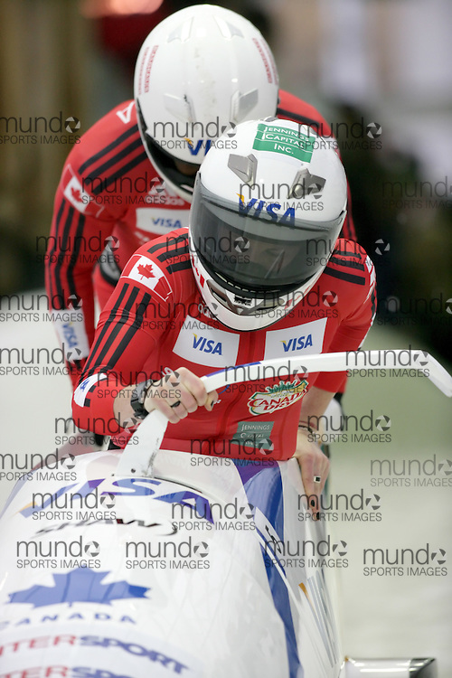 (November 21, 2009) Helen Upperton (front) and Shelly-Ann Brown of Canada push in the first run en route to a 6th place finish at  the Federation Internationale de Bobsleigh et de Togogganing (FIBT) two-man men's bobsled World Cup race at the Olympic Sports Complex in Lake Placid, New York.
