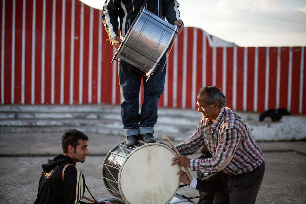 """Father Abdush (right) and his sons Mersid (left), Erdal ( behind) and Ergul (on top) during a drum session on a stage in front of the """"House of Culture"""" in Delcevo, Macedonia. The Roma family - father and his 3 sons - are well know for their drum perfomances and also they build their drums themselves."""