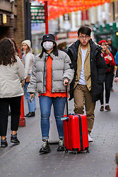 © Licensed to London News Pictures. 01/02/2020. London, UK. An Asian woman with suitcase is seen in London's Chinatown wearing face masks following the outbreak of Coronavirus in Wuhan, China. <br /> According to the Department of Health, 203 people have been tested in the UK, with 201 results coming back negative and two positive. One of the two people to test positive for is a student at the University of York. Photo credit: Dinendra Haria/LNP