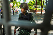 "20 MAY 2104 - BANGKOK, THAILAND:  A Thai soldier at a checkpoint on Rama I Road in Bangkok. The Thai Army declared martial law throughout Thailand in response to growing political tensions between anti-government protests led by Suthep Thaugsuban and pro-government protests led by the ""Red Shirts"" who support ousted Prime Minister Yingluck Shinawatra. Despite the declaration of martial law, daily life went on in Bangkok in a normal fashion. There were small isolated protests against martial law, which some Thais called a coup, but there was no violence.  PHOTO BY JACK KURTZ"