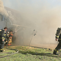 Adam Robison | BUY AT PHOTOS.DJOURNAL.COM<br /> Mooreville volunteer and Saltillo firefighters firght a house fire on county road 1562 Monday morning in Mooreville.