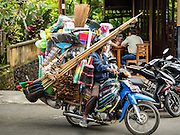 17 JULY 2016 - UBUD, BALI, INDONESIA: A man selling brooms and home supplies from a motorcycle on Jalan Wenara Wana, also known as Monkey Forest Road, in Ubud, Bali.       PHOTO BY JACK KURTZ