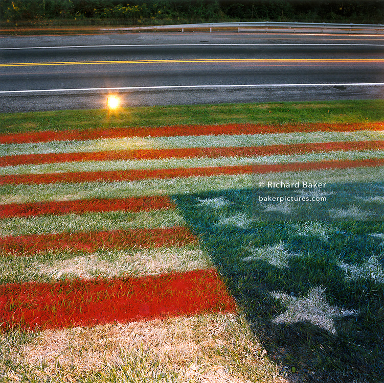 "Patriotic Americana - After 9/11. An aerosol American flag sprayed on a grassy knoll. In the week after the September 11th attacks, America sought to express their anger and patriotic unity. Evidence of a resilient nation was found on many roadsides. Here, a local garage owner has aerosol-sprayed the Stars and Stripes onto a grassy verge on Highway 422 in Sinking Spring, Pennsylvania..""These Colours Don't Run."" - From a New York City T-shirt..."
