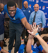 Former NBA play Felipe Lopez high-fives with students during a financial education and success program sponsored by NBA Cares and BBVA Compass at Crespo Elementary School, February 27, 2014.
